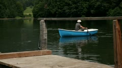 Young man in a boat on paddels fishing Stock Footage