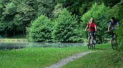 Young couple cycling in nature - stock footage