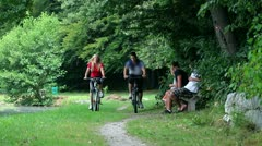 Young couple cycling in nature and passing family that sits on the bench - stock footage