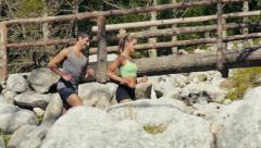 2of4 Young man and woman running on mountain trail, sport Stock Footage