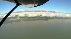 Aerial cloud view of distant Mt Redoubt Volcano Alaskan Wilderness light Stock Footage