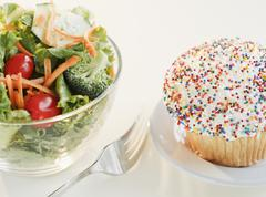 Comparison of cupcake and bowl of salad Stock Photos
