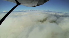 Aerial cloud view of distant mountain range remote Wilderness, light aircraft, Stock Footage