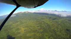 Aerial cloud view of distant Mt Redoubt Aleutian mountain range Alaskan Stock Footage