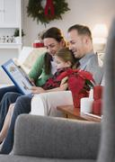 Stock Photo of Parents reading to daughter