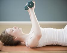 Woman exercising with dumbbells - stock photo