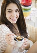Stock Photo of Brunette woman eating granola and yogurt