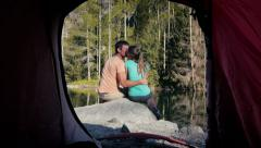Outdoor activity, young couple camping with tent near mountain lake Stock Footage