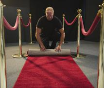 Bouncer rolling red carpet Stock Photos
