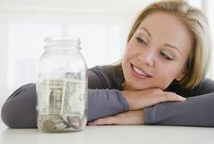 Stock Photo of USA, New Jersey, Jersey City, Young attractive woman watching improvised jar -