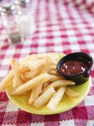 Stock Photo of Close up of french fries on checked table cloth