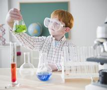 Boy (8-9) holding chemical flask in science lab Stock Photos