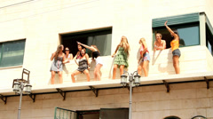 9 happy girls overlooks the Pride Parade from a balcony and dance Stock Footage