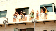 Stock Video Footage of 9 happy girls overlooks the Pride Parade from a balcony and dance