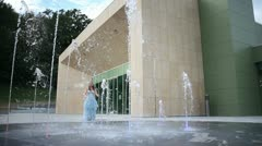 Woman in a beautiful dress playing with water fountain Stock Footage
