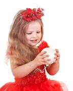 Girl in red dress holding christmas ball. Stock Photos