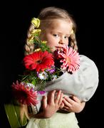 Child holding flowers and gas mask . Stock Photos