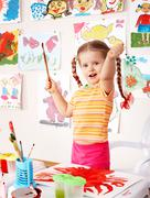 Stock Photo of child with picture and brush in playroom.