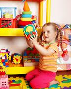 Child with puzzle and block  in playroom. Stock Photos