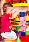 Stock Photo of child with puzzle, block and construction set in play room.