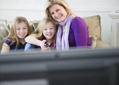 USA, Jersey City, New Jersey, mother and daughters (8-11) watching tv - stock photo