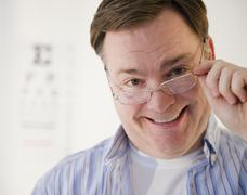USA, Jersey City, New Jersey, portrait of man lowering glasses Stock Photos