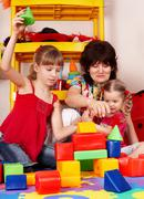 Stock Photo of children  with  block and senior woman in play room.