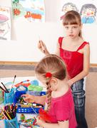 children  prescooler with colour pencil in play room. - stock photo