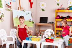 Group of children with colour pencil in play room. Stock Photos
