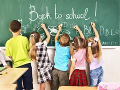 Children writing on blackboard. Stock Photos
