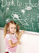 School child writing on black board. Stock Photos