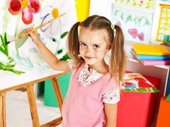 Child painting at easel. Stock Photos