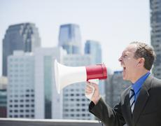 USA, New Jersey, Jersey City, Businessman shouting through megaphone Stock Photos