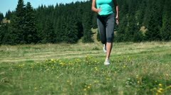 Close up of a woman tying up sholaces while jogging Stock Footage