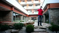 Shot a young man jumping in front of hotel when telling a story Stock Footage