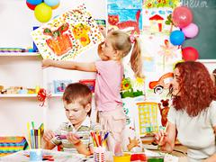 Stock Photo of child painting at easel.