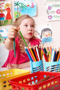 child painting by pencil in art class. - stock photo