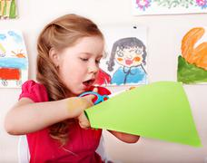 Stock Photo of child with scissors cut paper in play room.