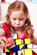 Stock Photo of child with block  in play room.