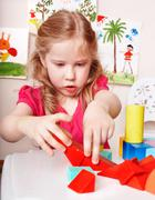 child preschooler play wood  block in play room. - stock photo