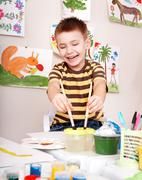 Child with brush draw red sun in play room. Stock Photos