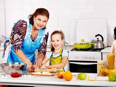 grandmother and grandchild baking cookies. - stock photo