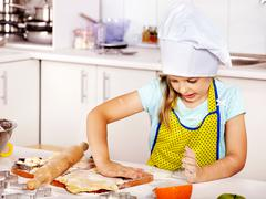 Child knead dough at kitchen. Stock Photos
