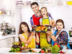 Happy family with grandmother at kitchen. Stock Photos