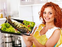 woman prepare fish in oven. - stock photo