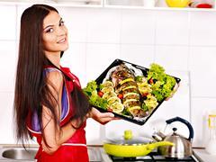 Stock Photo of woman prepare fish in oven.