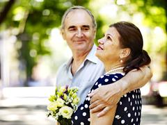 happy old couple with flower. - stock photo