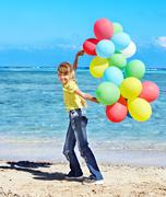 Stock Photo of child playing with balloons at the beach