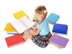 Child with pile of books reading on floor. Stock Photos