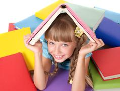 Child with pile of books on head. Stock Photos
